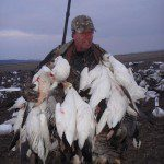 Happy hunter with a game strap full of snow geese.